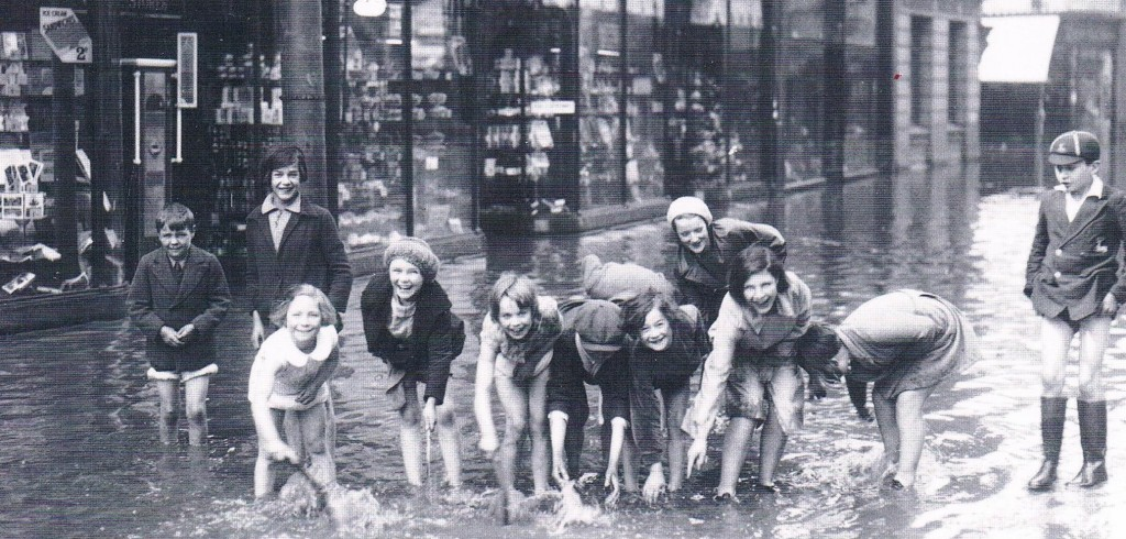Derby, 1932. Children seeing the lighter side to floods outside Woolworths on Victoria Street. From our Derby Memories book.