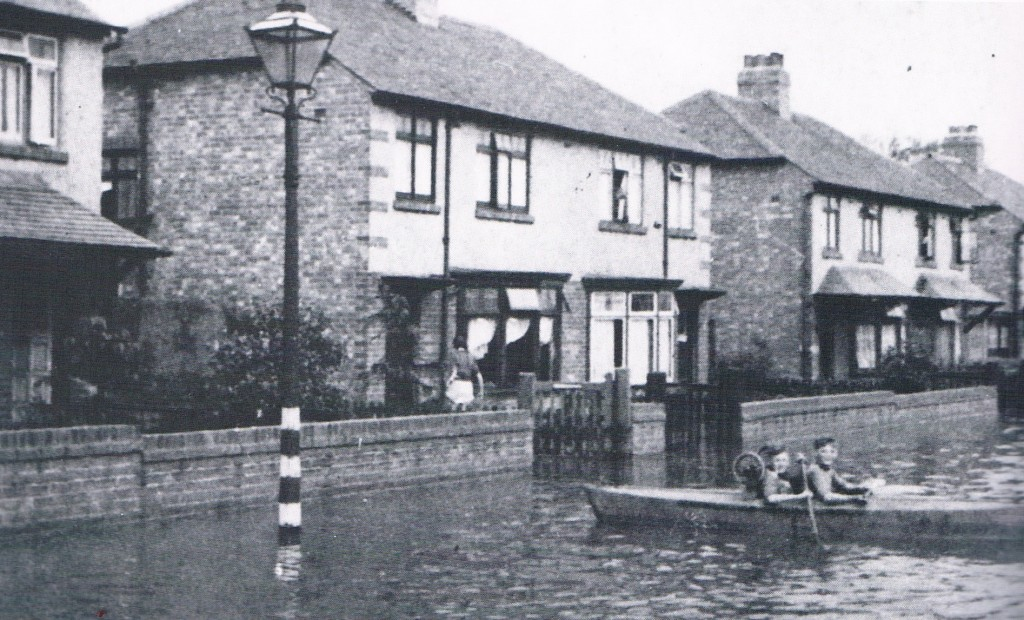 Newcastle, 1941 Chatsworth Gardens, Westerhope, completely under water. 2 boys sail a homemade boat across the street! Taken from our Newcastle and Tyneside books.